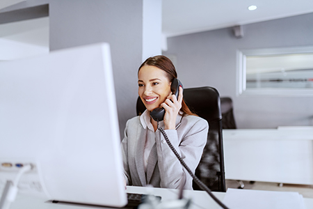 Caucasian businesswoman with long brown hair and in formal wear using computer and talking on the phone